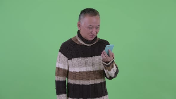 Thumbnail for Happy Mature Japanese Man Using Phone and Looking Surprised