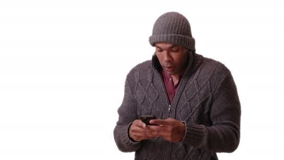 Thumbnail for An African American man stands trembling on a white background on his smart phone