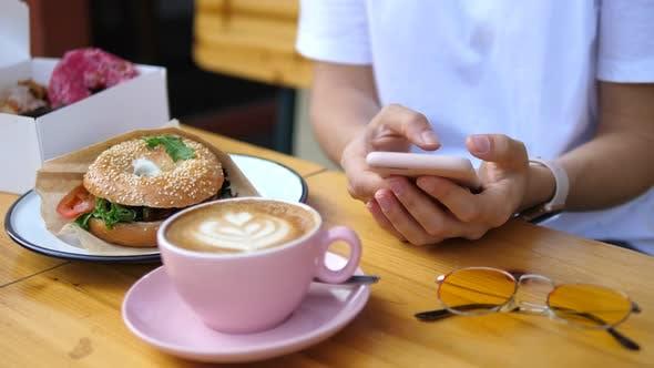 Weibliche Hände mit Handy Beim Frühstück Mit Kaffee Und Bagel