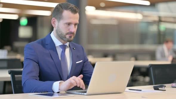 Middle Aged Businessman Feeling Shocked While Using Laptop