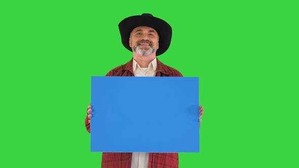 Thumbnail for Smiling Senior Man in a Hat Holding Blank Placard on a Green Screen, Chroma Key.