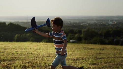 Video of boy running with a plane outdoors. Shot with RED helium camera in 8K.
