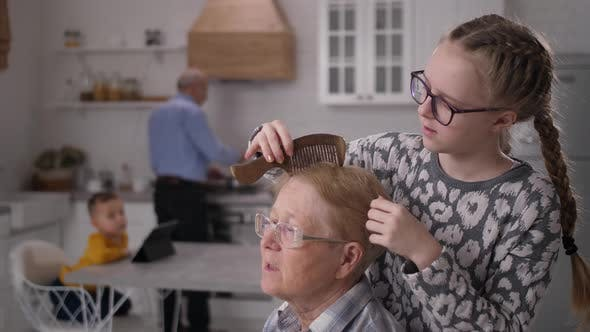 Kind Granddaughter Combing Hair of Disabled Granny