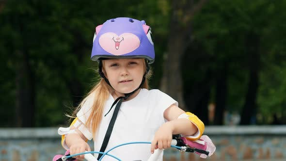 Thumbnail for Portrait of A Little Girl in A Purple Bicycle Helmet