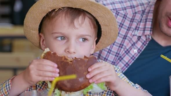 Kids Food, Little Male Child Enjoys Tasty Unhealthy Junk Food Eats Sleepy Meat Burger While Relaxing