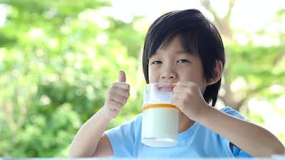 Cute Asian Child With A Glass Of Milk
