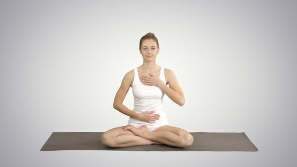 Thumbnail for Yoga girl breathing in lotus pose with her hands on her