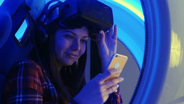 Thumbnail for Cheerful Girl in Virtual Reality Headset Checking Her Selfies on the Phone