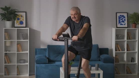 Sport und gesunder Lebensstil beim mittleren und hohen Alter trainiert zu Hause auf stationärem Fahrrad