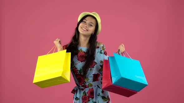 Thumbnail for Girl Dancing with Colorful Packages in Their Hands. Pink Background. Slow Motion