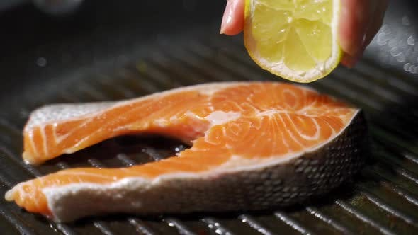 Thumbnail for Pan-fried Salmon, Trout. Chef Pours Salmon Steak with Lemon Juice