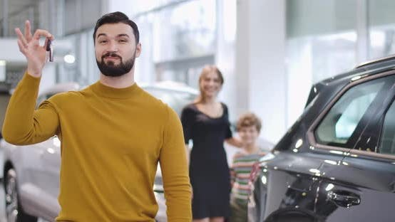 Thumbnail for Portrait of Satisfied Caucasian Man Showing Car Keys, Crossing Hands, and Smiling