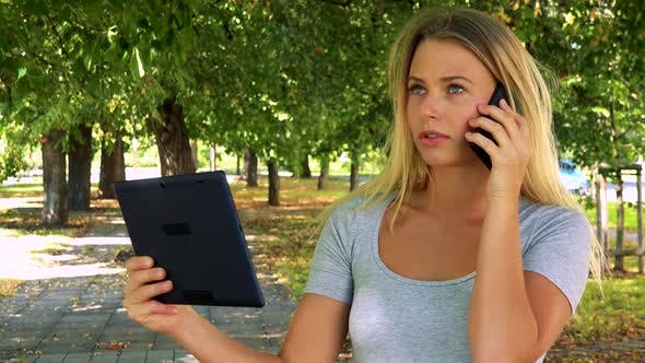 Thumbnail for Young Pretty Blond Woman Works on Tablet and Phone with Smartphone - Park with Trees in Background