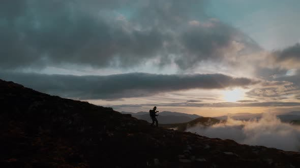 Thumbnail for Man Walk on Edge of Epic Cliff at Sunset in Clouds
