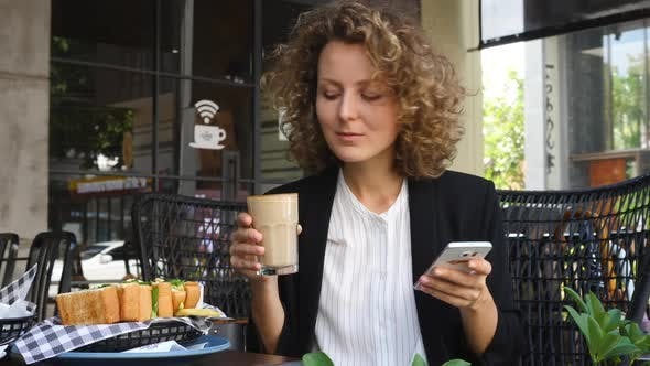 Thumbnail for Young Business Woman Using Smartphone And Drinking Coffee