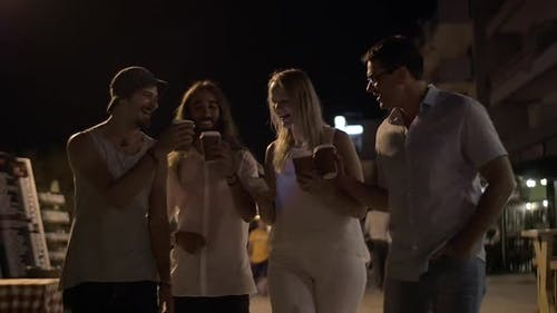 Friends toasting with coffee cups in night street