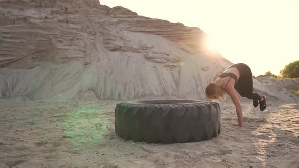Thumbnail for Girl on Sand Quarry Jumping Burpee with push-UPS Through the Wheel in the Sand