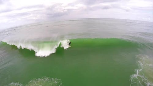 Aerial view of a surfer riding a wave while surfing
