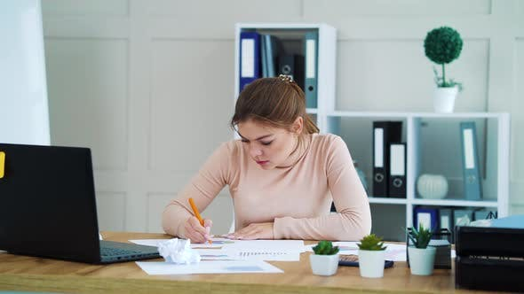 Woman Writing on Paper and Crumpling It