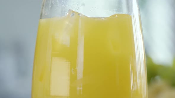 Orange Juice With Ice Cubes Rotating In Glass