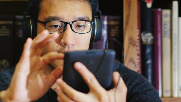 Thumbnail for Portrait of an Asian Man in Glasses. It Uses a Tablet in the Library. He Sits on the Background of