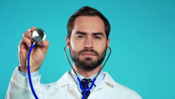 Thumbnail for Portrait of Man in Professional Medical Coat Using Stethoscope Isolated on Blue