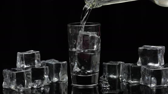 Thumbnail for Pouring Up Shot of Vodka From a Bottle Into Glass Black Background