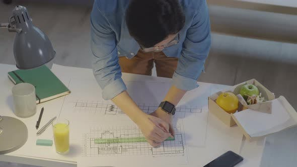 Man Drawing Architectural Plan at Office Desk