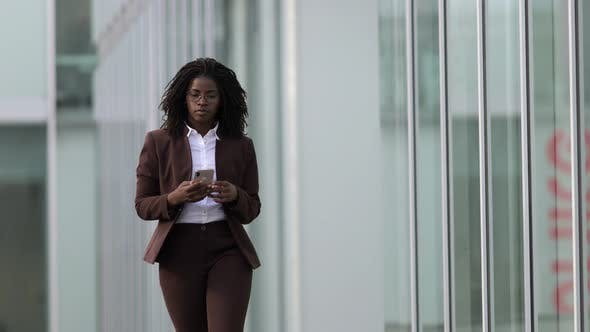 Thumbnail for Serious African American Woman Using Smartphone During Stroll