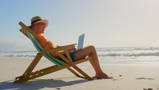 Thumbnail for Frau mit Hut mit Laptop am Strand in der Sonne 4k