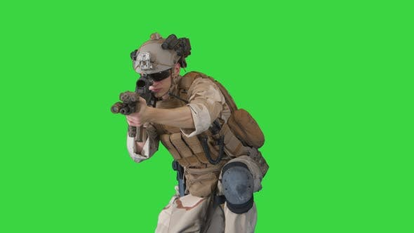 US Military Marine Shooting From Sitting Position on a Green Screen, Chroma Key.