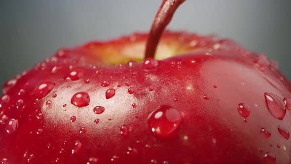 Thumbnail for Water droplets on red apple as it spins