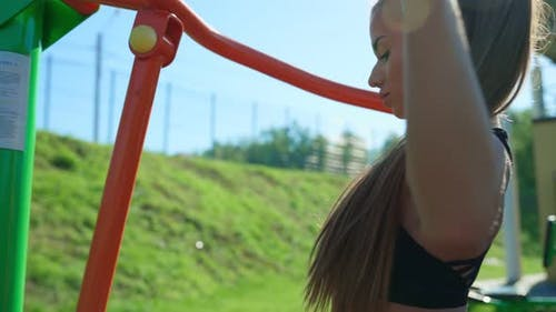 Woman Practicing Lat Pull Downs at Sports Ground