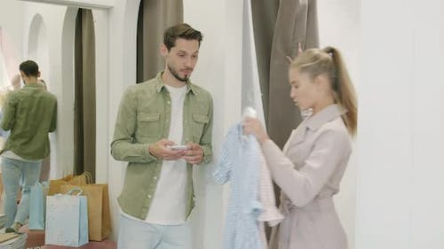 Generous Young Man Using Smartphone Then Talking to Wife Near Fitting Room While Woman Laughing
