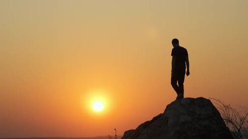 Silhouette of a man hiker climbing alone down from a big stone at sunset in mountains.