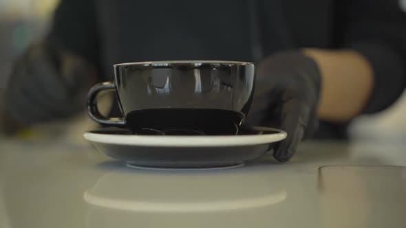 Thumbnail for Unerkennbar Barista in Schutzhandschuhen nähert sich Kaffeetasse an die Kamera. Nahaufnahme von Heißgetränk