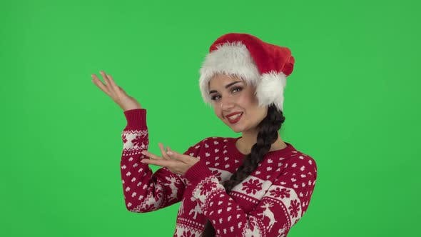 Portrait of Sweety Girl in Santa Claus Hat Is Talking and Pointing Side Hand for Something, Copy