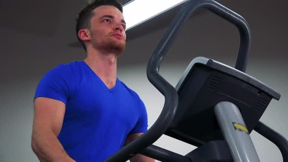Thumbnail for A Young Fit Man Trains on a Machine in a Gym - Closeup From Below