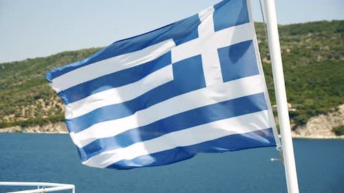 Greek Flag Flutters in the Wind with Sea and Island in Background Greece