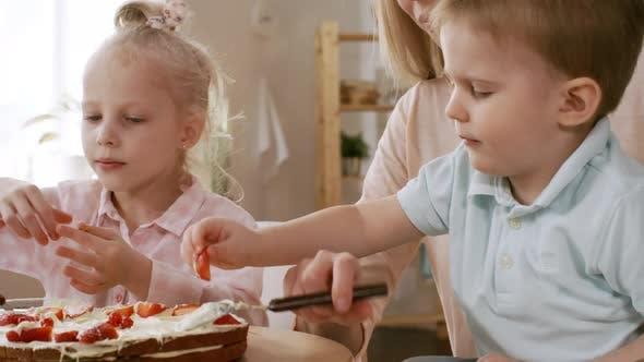 Thumbnail for Caucasian Siblings Adding Berries to Layered Cake