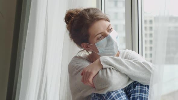 Thumbnail for Langweilig Frau in medizinischer Maske sitzt auf Schwelle und Blick durch Fenster