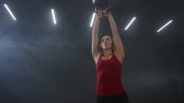 Thumbnail for Woman Performing Weightlifting Exercise with Kettlebell