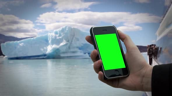 Thumbnail for Hand holding an Old Smartphone with Green Screen near an Iceberg.