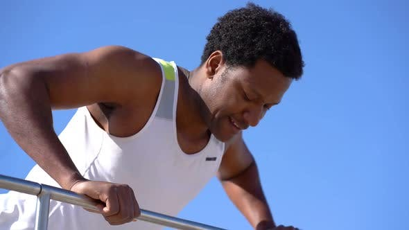 Cover Image for Smiling Sporty Man Training on Railing Against Blue Sky