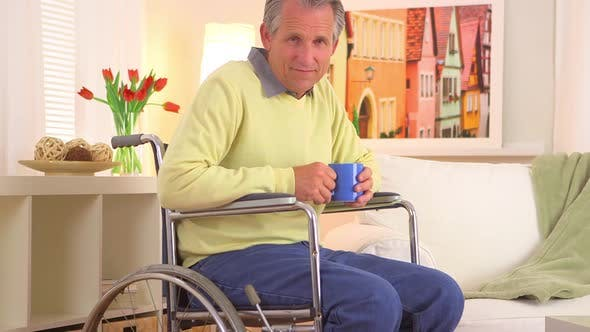 Thumbnail for Old man sitting in wheelchair with coffee