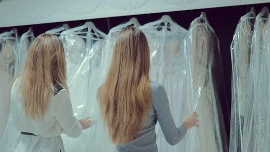 Mädchen schauen sich Brautkleider im Salon an