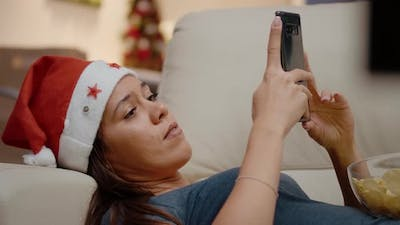 Close Up of Woman with Santa Hat Holding Smartphone