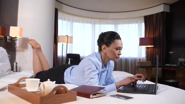 Woman Networking on Laptop Lying on Bed in Suite