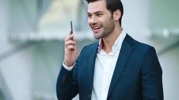 Thumbnail for Portrait Businessman Using Smartphone. Man Smiling with Phone in Hand Outdoors