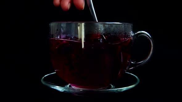 Zubereitung von Hibiskus-Tee in einer Glastasse.